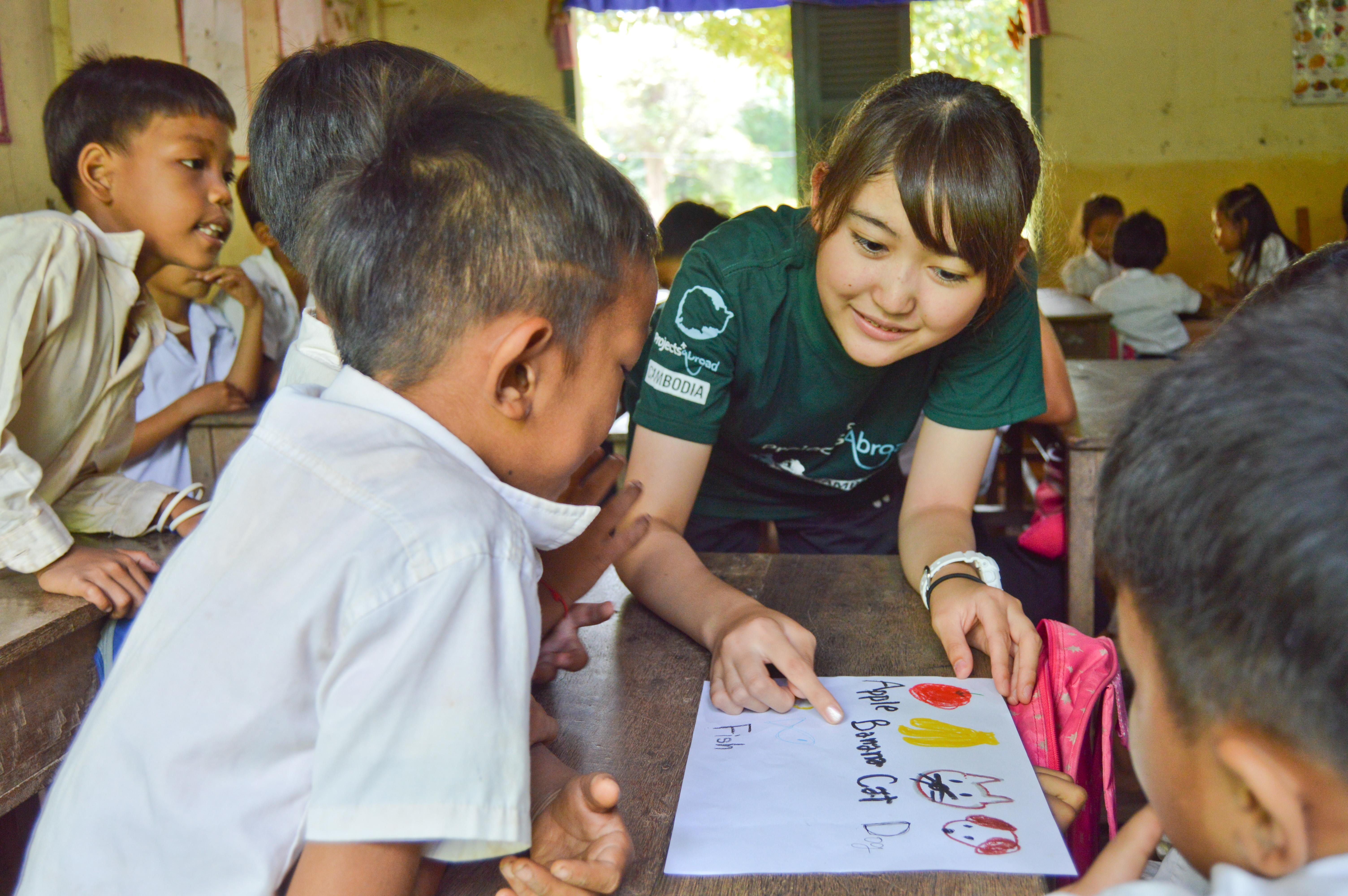 A teenage volunteer working with children in Cambodia helps a child with his English animal and fruit sight words.